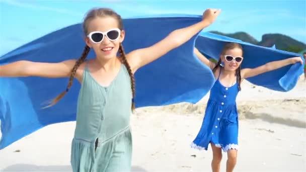 A kislányok szórakoznak a strandtörölközővel a trópusi vakáció alatt