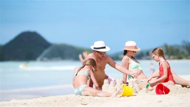 Family making sand castle and enjoying vacation at tropical white beach