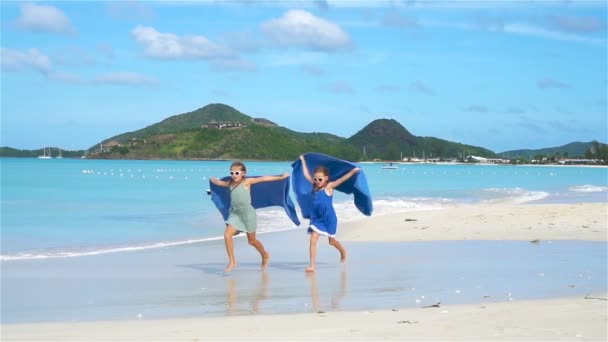 Little girls have fun with beach towel during tropical vacation