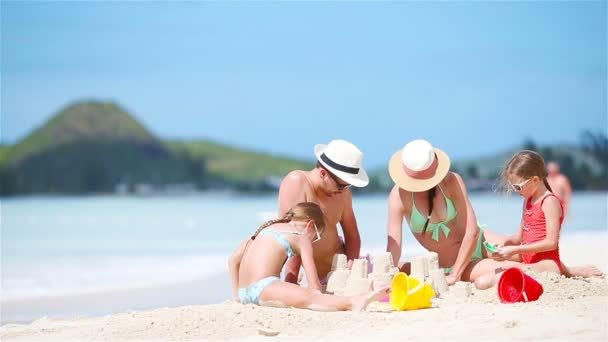 Family making sand castle on white beach on summer holidays