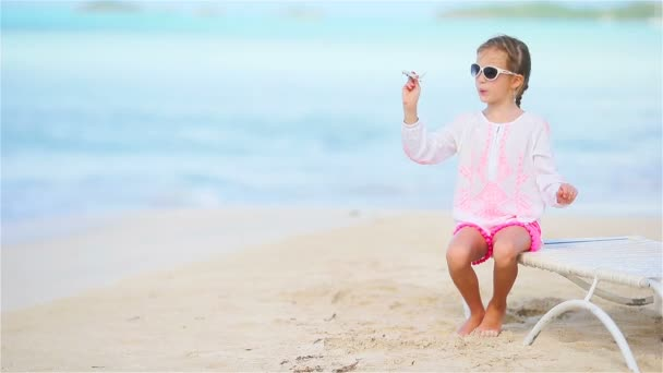 glückliches kleines Mädchen mit Spielzeugflugzeug in den Händen am weißen Strand