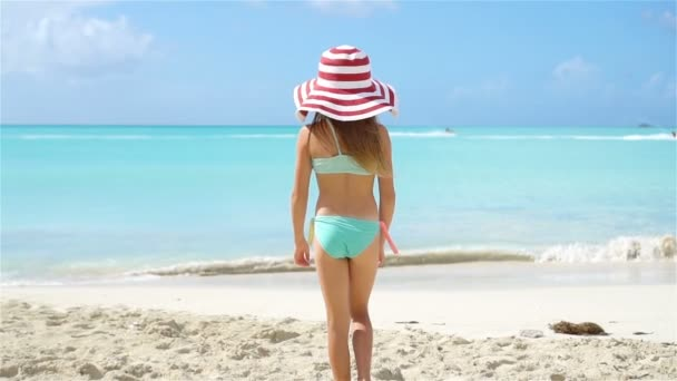 Imádnivaló kicsi lány séta a fehér homokos strand, nagy kalap
