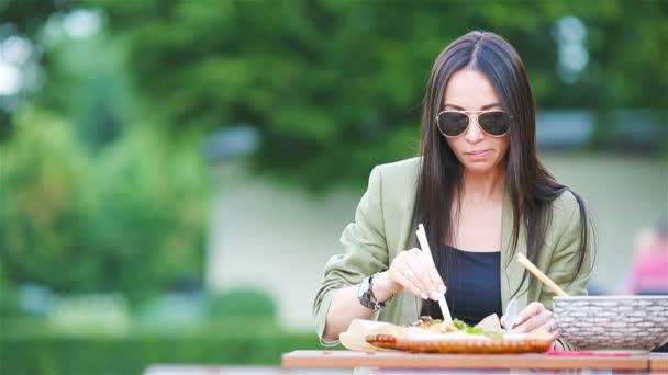 junge Frau isst Nudeln zum Mitnehmen auf der Straße