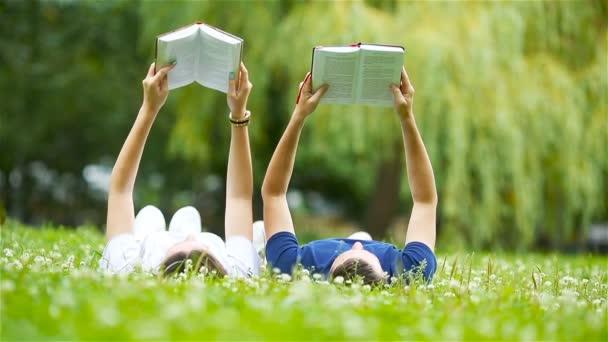 Uvolněné mladý pár čtení knih vleže na trávě