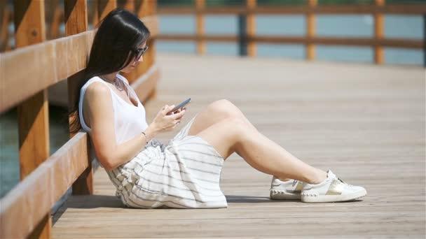 Roztomilá žena čte textovou zprávu na mobilním telefonu, zatímco sedí v parku.