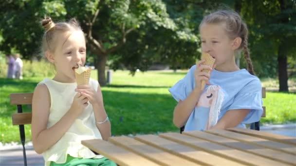 Kleine Mädchen essen im Sommer Eis im Freien in einem Café