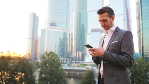 Junger Mann aus Kaukasien hält Smartphone für Geschäftsarbeit.