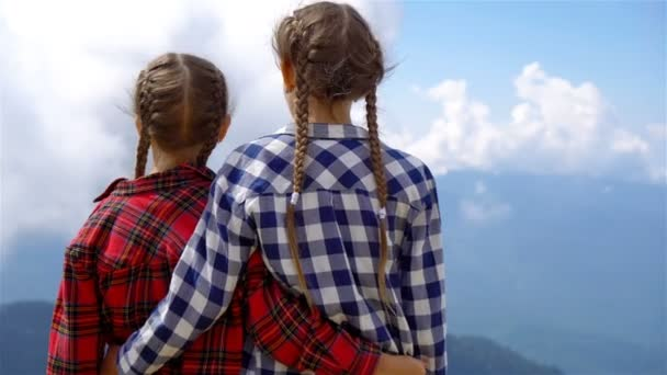 Adorable happy little girls in mountains in the background of beautful landscape