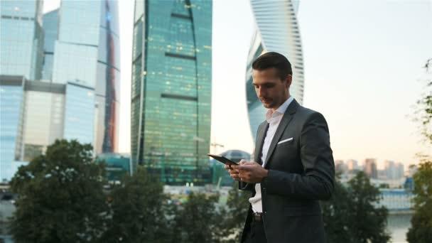 Kaukázusi fiatalember gazdaság üzleti munka okostelefon.
