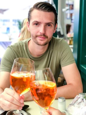 Young boy with a glass of aperal clink glasses with a glass of his beloved girl