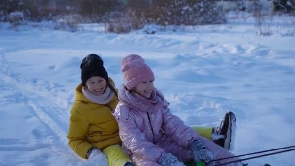 entzückende kleine glückliche Mädchen Rodeln im Winter verschneiten Tag.