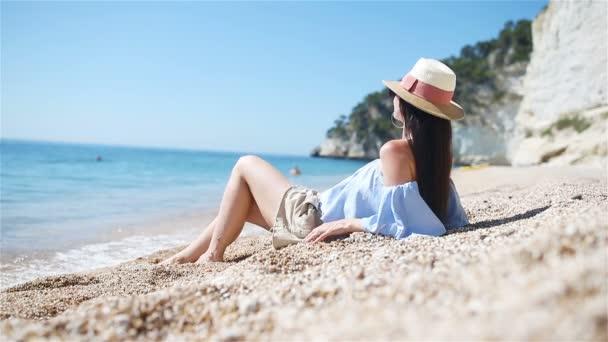 Fiatal gyönyörű nő fehér homokos trópusi tengerparton. Kaukázusi lány kalap háttérben a tenger