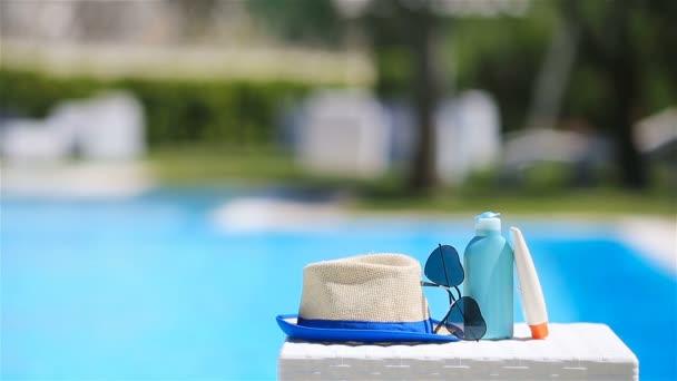 Napkrém, kalap, napszemüveg a medence közelében