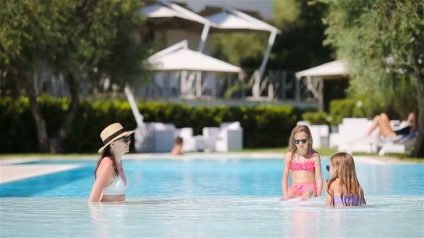 Anya és két gyerek élvezi a nyári vakációt a luxus uszodában