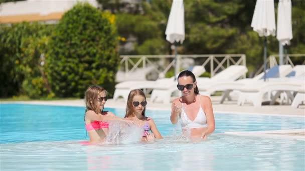 Matka a dvě děti si užívají letní dovolenou v luxusním bazénu