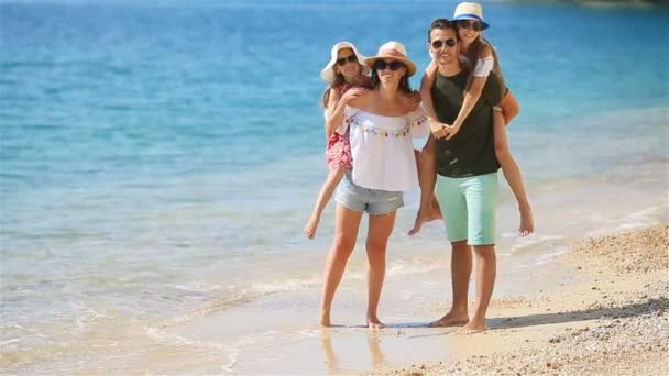 Young family on vacation walking by the sea