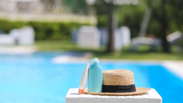 Krém, klobouk, sluneční brýle u bazénu