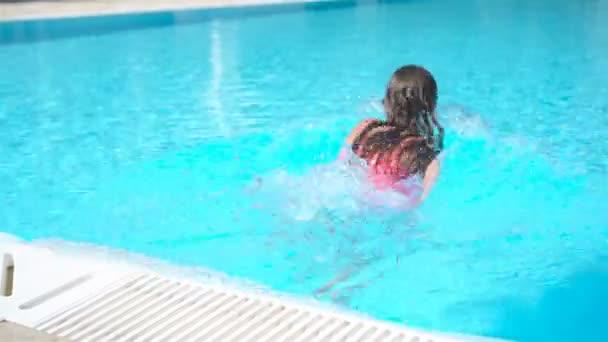 Rozkošná holčička plavání v venkovním bazénu