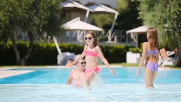 Otec a dvě děti si užívají letní prázdniny v luxusním bazénu