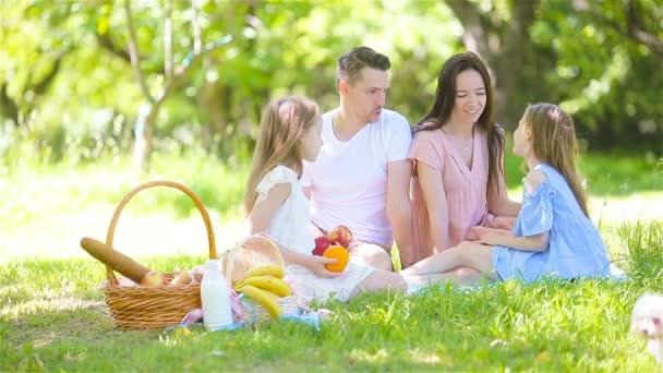 Šťastná rodina na pikniku v parku za slunečného dne