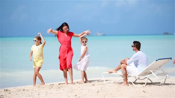 Young family on vacation have a lot of fun. Mother dancing on the beach with her beautiful kids