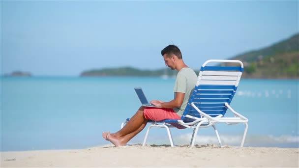 Fiatal férfi laptop trópusi karibi tengerparton. Az ember ül a szoláriumban, a számítógép, és dolgozik a strandon