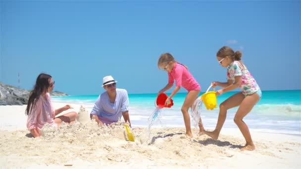 Rodina se dvěma dětmi dělat hrad z písku na tropické pláži