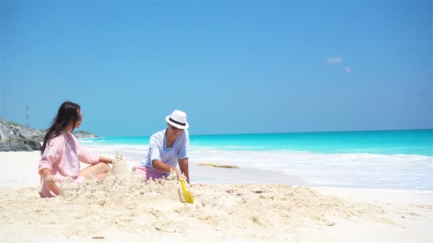 Family of four making sand castle at tropical beach