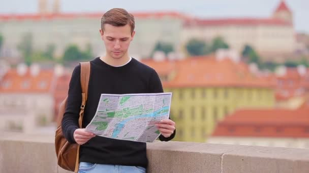 Man tourist with a city map and backpack in Europe. Caucasian boy looking with map of European city in search of attractions.