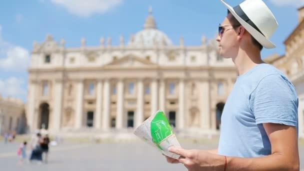 Mladý muž s mapou města ve Vatikánu a bazilikou sv. Petra, Řím, Itálie. Cestovní turista s mapou venku během dovolené v Evropě.