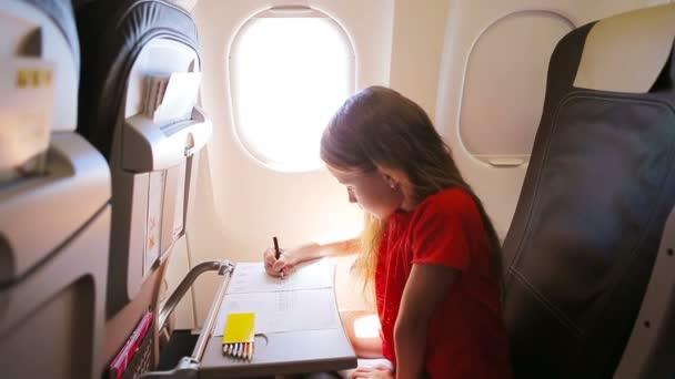 Rozkošná holčička cestuje letadlem. Dětská kresba obrázek s barevnými tužkami sedí u okna letadla