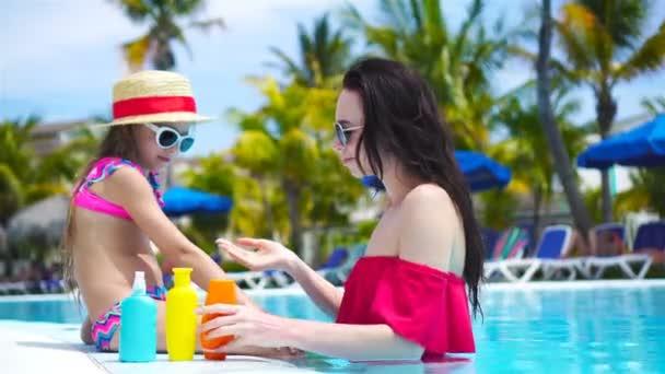 Mladá matka nanáší opalovací krém na dětský nos v bazénu. Koncept ochrany před ultrafialovým zářením