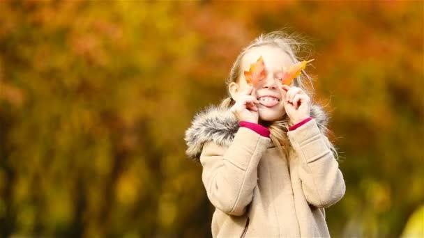 Portrét rozkošné holčičky venku v krásném teplém dni se žlutým listem na podzim