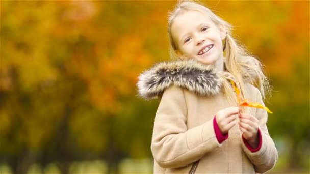 Portrait of adorable little girl outdoors at beautiful warm day with yellow leaf in fall