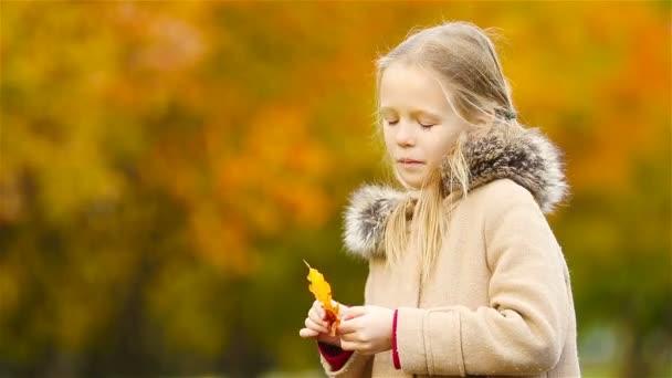 Porträt eines entzückenden kleinen Mädchens im Freien an einem schönen warmen Tag mit gelbem Blatt im Herbst