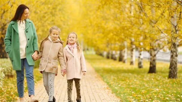 Family of mother and kids in fall. Young mother and little girls enjoy warm autumn