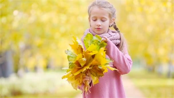 Portrét rozkošné holčičky se žlutými a oranžovými listy kytice venku na krásném podzimním dni