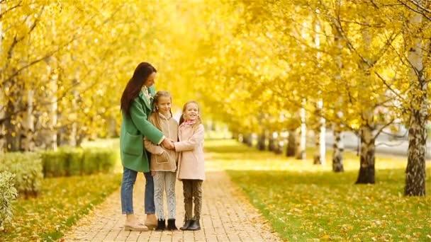 Az anya és a gyerekek családja ősszel. Fiatal anya és kislányok élvezik a meleg őszt