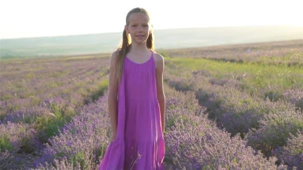 Žena v levandulové květy pole při západu slunce v bílých šatech a klobouku