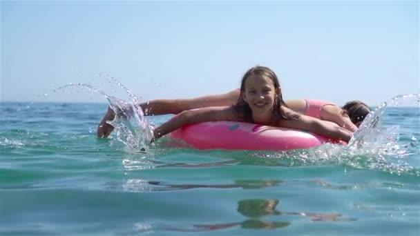 Rozkošná dívka na nafukovací matraci v moři
