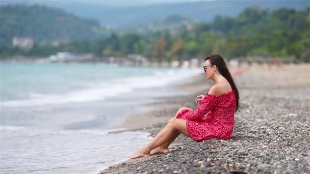 Žena leží na pláži a užívá si letní prázdniny při pohledu na moře
