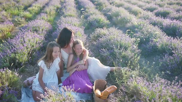 Family in lavender flowers field at sunset in white dress and hat