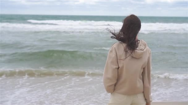 Mladá žena na pláži v bouři