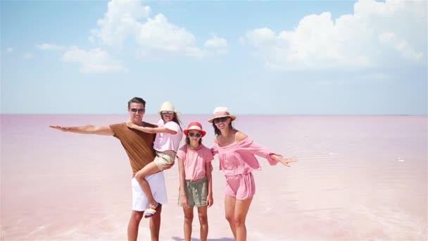 Rodinná procházka růžovým slaným jezerem za slunečného letního dne.