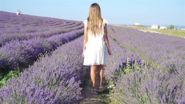 Dívka v levandulové květy pole v bílých šatech
