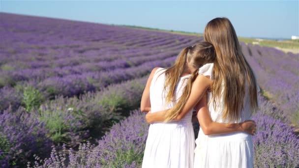 Dívky v levandulových květinách pole při západu slunce v bílých šatech