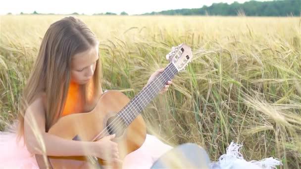 Rozkošná školačka v pšeničném poli na teplém a slunečném letním dni