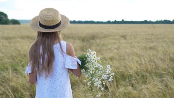 Adorable preschooler girl walking happily in wheat field on warm and sunny summer day