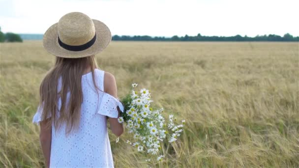 Beautiful girl in wheat field with a bouquet of chamomile in hands