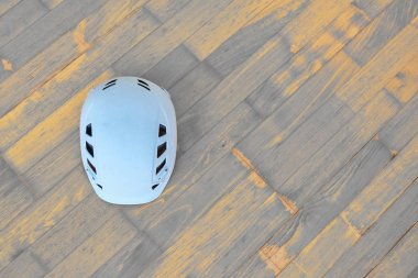 White climbing helmet (also used in alpine or industrial constructions) on wooden background with diagonal timber planks in gray and orange. Copy space on the right.